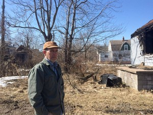 Michael Score, president of Hantz Farms, stands on the site of a planned farm in inner-city Detroit, on Friday, March 21, 2014, with a burned and abandoned house in front of him and a garage behind him that was just discovered last week while clearing out wild brush. THE CANADIAN PRESS/Alex Panetta