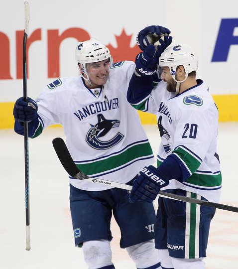 Canucks forwards Alex Burrows and Chris Higgins celebrate a goal