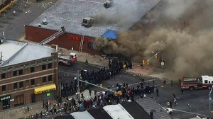 In this frame from video provided by WJLA, smoke rises from a store on April 27, 2015, during unrest following the funeral of Freddie Gray in Baltimore. Rioters plunged part of Baltimore, torching a pharmacy, setting police cars ablaze and throwing bricks at officers. WJLA via AP