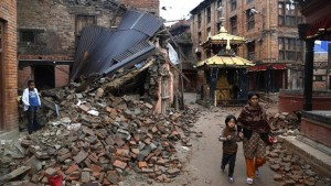 In this Thursday, April 30, 2015 photo, a Nepalese woman and a child walk near rubble of a collapsed building in Bhaktapur Durbar Square, a UNESCO World Heritage Site, on the outskirts of Kathmandu, Nepal. (AP Photo/Manish Swarup)