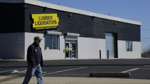 FILE - In this March 12, 2015 file photo, a man walks past a Lumber Liquidators store in Philadelphia. Lumber Liquidators CEO Robert Lynch has abruptly quit the company that is embroiled in an investigation over products imported from China. Shares tumbled more than 18 percent in premarket trading Thursday, May 21, 2015. (AP Photo/Matt Slocum)