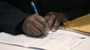 FILE - In this April 22, 2015 file photo, a job seeker fills out an application during a National Career Fairs job fair in Chicago. The Labor Department releases weekly jobless claims on Thursday, May 21, 2015. (AP Photo/M. Spencer Green, File)