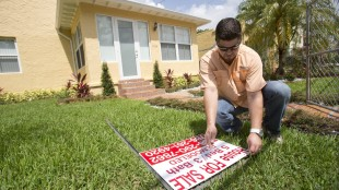 In this Friday, April 24, 2015 photo, Robert Almirall, director of marketing and special assets coordinator for Mederos & Associates Real Estate Inc., prepares to put up a sign in front of a home in the Shenandoah neighborhood of Miami. The National Association of Realtors releases existing home sales for April on Thursday, May 21, 2015. (AP Photo/Wilfredo Lee)