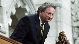 Eugene Melnyk, owner of the NHL's Ottawa Senators, stands in the visitors gallery as he is recognized in the House of Commons at the conclusion of Question Period on Parliament Hill, in Ottawa on March 4, 2014. Doctors say Ottawa Senators owner Eugene Melnyk is recovering well after his liver transplant earlier this week at a Toronto hospital, as is the anonymous donor who made the life-saving surgery possible. THE CANADIAN PRESS/Fred Chartrand