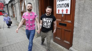 Partners Adrian, centre left and Shane, leave a polling station after casting their vote in Drogheda, Ireland, Friday, May 22, 2015. Ireland began voting Friday in a referendum on Gay marriage which will require an amendment to the Irish constitution. Opinion polls throughout the two-month campaign suggest the government-backed amendment should be approved by the required majority of voters when results are announced Saturday. (AP Photo/Peter Morrison)
