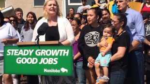 Manitoba Family Services Minister Kerri Irvin-Ross (center) and Jobs and The Economy Minister Kevin Chief (right, blue shirt) announce increased housing subsidies Friday, May 22, 2015 behind a sign bearing the government's Steady Growth, Good Jobs slogan. The slogan has been used in government ads that the opposition says amounts to partisan promotion for the NDP. THE CANADIAN PRESS/Steve Lambert