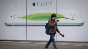 A man looks at his mobile phone while walking past an iPhone 6 advertisement outside the headquarters of Telus in Vancouver, B.C., on Thursday December 18, 2014. Consumers lodged hundreds of complaints against telecom companies between January and August of 2013. THE CANADIAN PRESS/Darryl Dyck