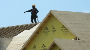 A construction worker works on a new home under construction in Oakville, Ont. on Friday, May 22, 2015. Lower crude prices are expected to help contribute to a split in the Canadian housing market that will see oil-producing provinces slow but others gain ground, Canada Mortgage and Housing Corp. said Monday THE CANADIAN PRESS/Richard Buchan