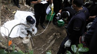 Malaysian police forensic team members inspect a freshly exhumed human body from an unmarked grave in Wang Burma at the Malaysia-Thailand border outside Wang Kelian, Malaysia, Tuesday, May 26, 2015. Malaysian forensic teams exhumed the body at an abandoned camp that was used by human traffickers, the first of what police predicted would be more grim findings as they combed through a cluster of jungle camps on the border with Thailand. (AP Photo/Joshua Paul)