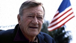 """FILE - This 1978 file photo shows actor John Wayne. Wearing a brown plaid coat worn by Wayne in 1945's """"Flame of Barbary Coast,"""" Republican Lt. Gov. Dan Patrick has declared a day in honor of the quintessential screen cowboy as he presided over the Senate Tuesday, May 26, 2015. He declared it John Wayne Day in Texas to mark the Hollywood legend's 108th birthday and named the actor an honorary Texan. (AP Photo, File)"""