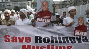 Indonesian Muslim protesters hold defaced posters of Myanmar's radical Buddhist monk Ashin Wirathu during a protest demanding an end to the violence against ethnic Rohingyas in Rakhine State, outside the Embassy of Myanmar in Jakarta, Indonesia, Wednesday, May 27, 2015. In the last three years, hundreds of minority Rohingya Muslims have been killed and hundreds of thousands others others are now living under apartheid-like conditions in crowded camps or forced to flee their homes to avoid persecution in Buddhist-majority Myanmar. (AP Photo/Achmad Ibrahim)