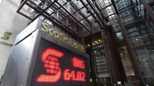 Scotiabank, one of Canada's largest banks, says it will review its involvement in sponsoring CONCACAF in the wake of corruption allegations against senior FIFA officials. An electronic sign posting financial data is shown outside the Scotiabank building in Toronto, Thursday, April 9, 2015. THE CANADIAN PRESS/Frank Gunn