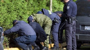 RCMP officers search the property surrounding an apartment building where six people died in a mulitple homicide in Surrey, B.C. Wednesday, Oct. 24, 2007. Two men convicted of first-degree murder in a mass execution that left six people dead are suing the British Columbia government for their alleged mistreatment in prison.Cody Haevischer and Matthew Johnston were also convicted of conspiracy in the October 2007 deaths in a Surrey highrise. THE CANADIAN PRESS/Jonathan Hayward