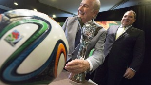 """FIFA President Sepp Blatter, left, pretends to shine the trophy with his suit jacket sleeve while posing for photographs with Canadian Soccer Association President Victor Montagliani following the opening press conference for the FIFA Women's Under 20 World Cup in Toronto, Ontario on Monday, Aug. 4, 2014. Montagliani has been named to a special CONCACAF committee charged with """"evaluating and sustaining"""" all of the confederation's business operations of the wake of FIFA's mushrooming corruption scandal. THE CANADIAN PRESS/Peter Power"""