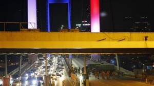 "Turkish soldiers block Istanbul's iconic Bosporus Bridge on Friday, July 15, 2016, lit in the colours of the French flag in solidarity with the victims of Thursday's attack in Nice, France. A group within Turkey's military has engaged in what appeared to be an attempted coup, the prime minister said, with military jets flying over the capital and reports of vehicles blocking two major bridges in Istanbul. Prime Minister Binali Yildirim told NTV television: ""it is correct that there was an attempt,"" when asked if there was a coup. (AP Photo/Emrah Gurel)"