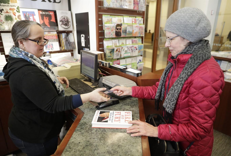 Rebecca Burgess, left, sells a copy of the book